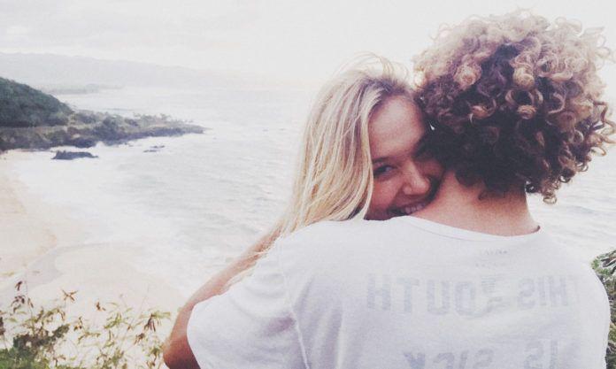 Blondynka przytula się do chłopaka z lokami w białej koszulce