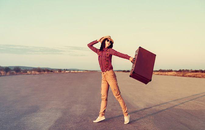 Dziewczyna w jasnych rurkach, czerwonej koszuli stoi z walizką na środku drogi