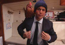 Brunet w niebieskiej czapce, garniturze z kurą na ramieniu
