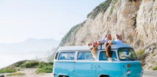 Dwie dziewczyny leżą na niebieskiej ciężarówce na tle skał