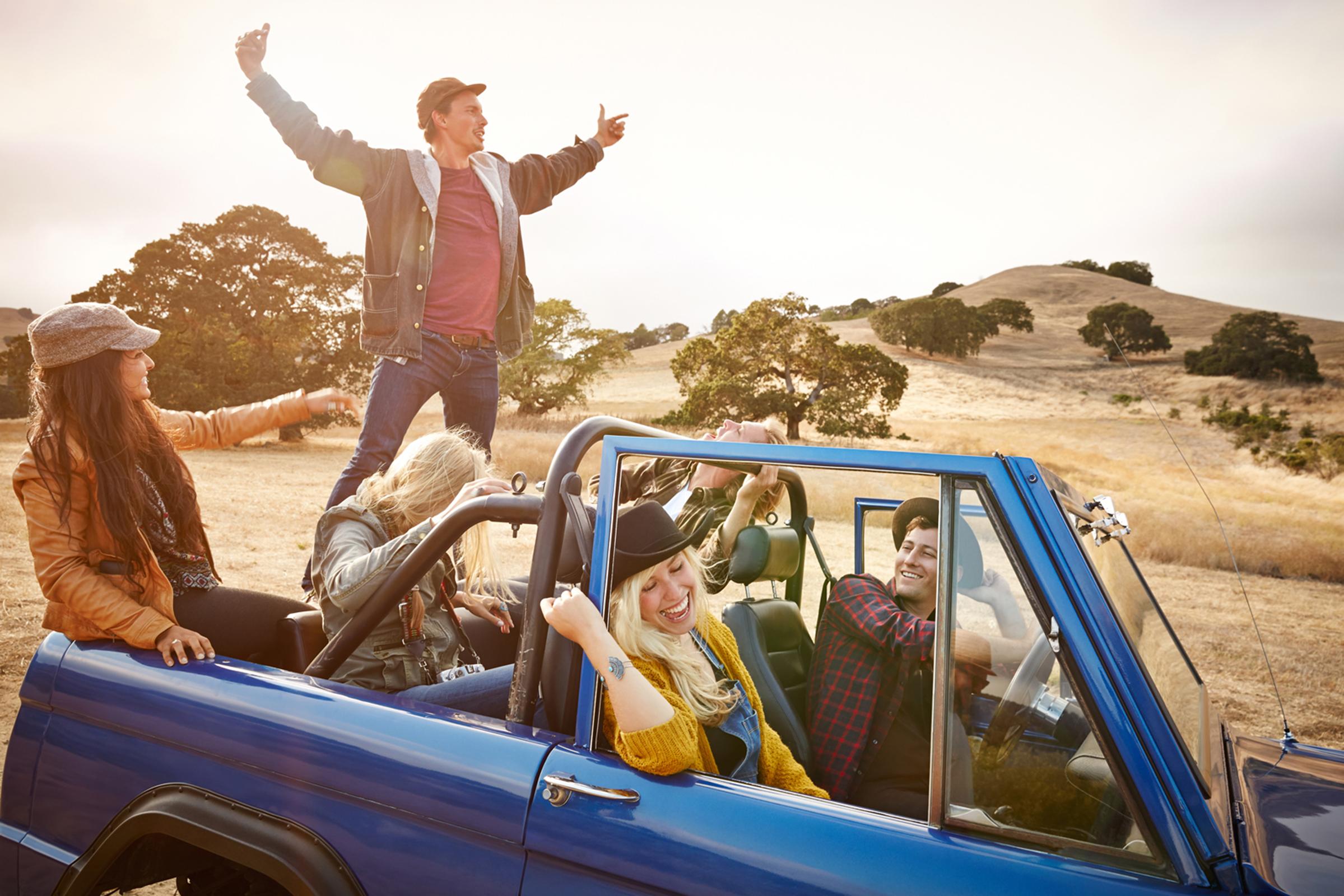 Grupa znajomych w terenowym niebieskim aucie na sawannie, chłopak stoi w bagażniku