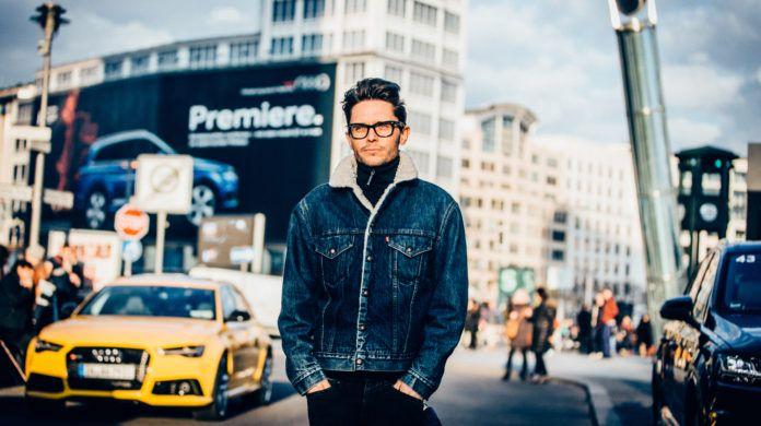 Mężczyzna w kurtce z futerkiem i w okularach na tle miasta