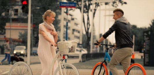 Kobieta w białej sukience i mężczyzna w czarnej kurtce, kolorowa hulajnoga