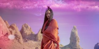 Kobieta w pomarańczowej sukience na tle skał i różowego nieba