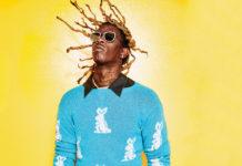 Czarnoskóry raper z dredami w niebieskim swetrze na żółtym tle