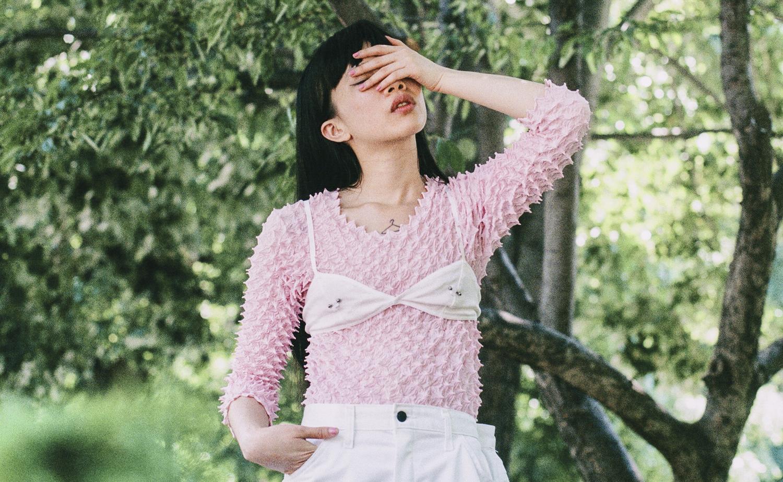 Azjatka ubrana w różowy sweter i biały biustonosz zakrywa twarz dłonią