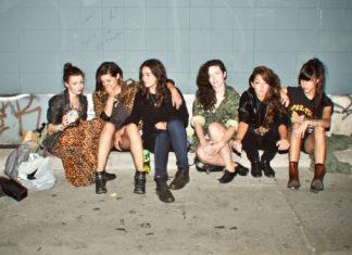 Grupa dziewczyn w streetwearowych ciuchach siedzi na ulicy przy murku