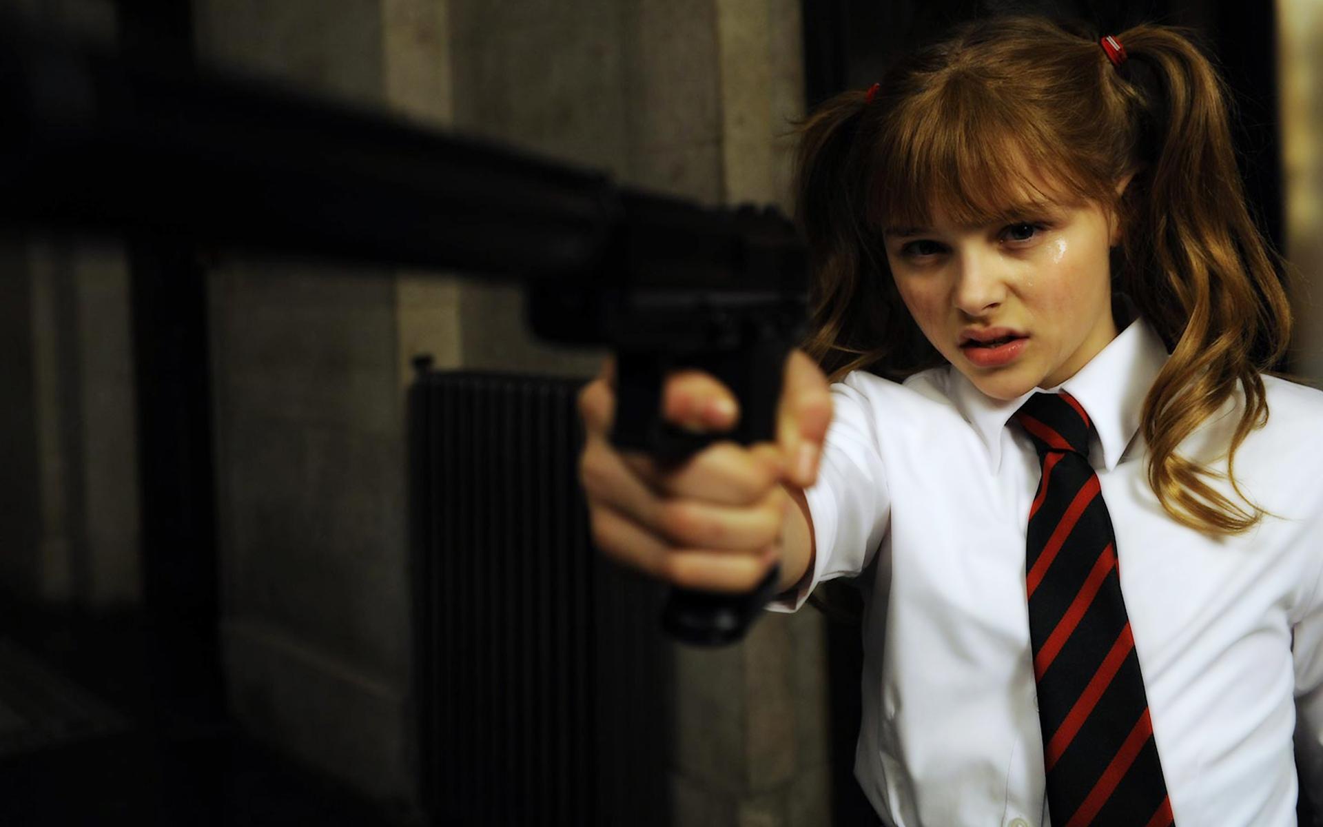 Dziewczynka w mundurku celuje pistoletem