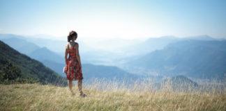 Dziewczyna w czerwonej sukience na łące patrzy na góry