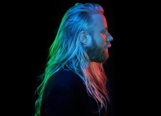 Mężczyzna z długimi włosami na czarnym tle