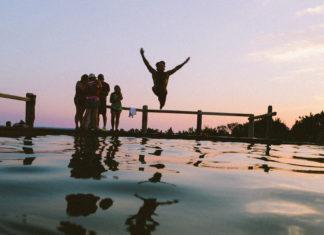 Grupa ludzi nad wodą, chlopak skacze