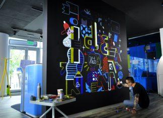 Artysta maluje mural klęcząc
