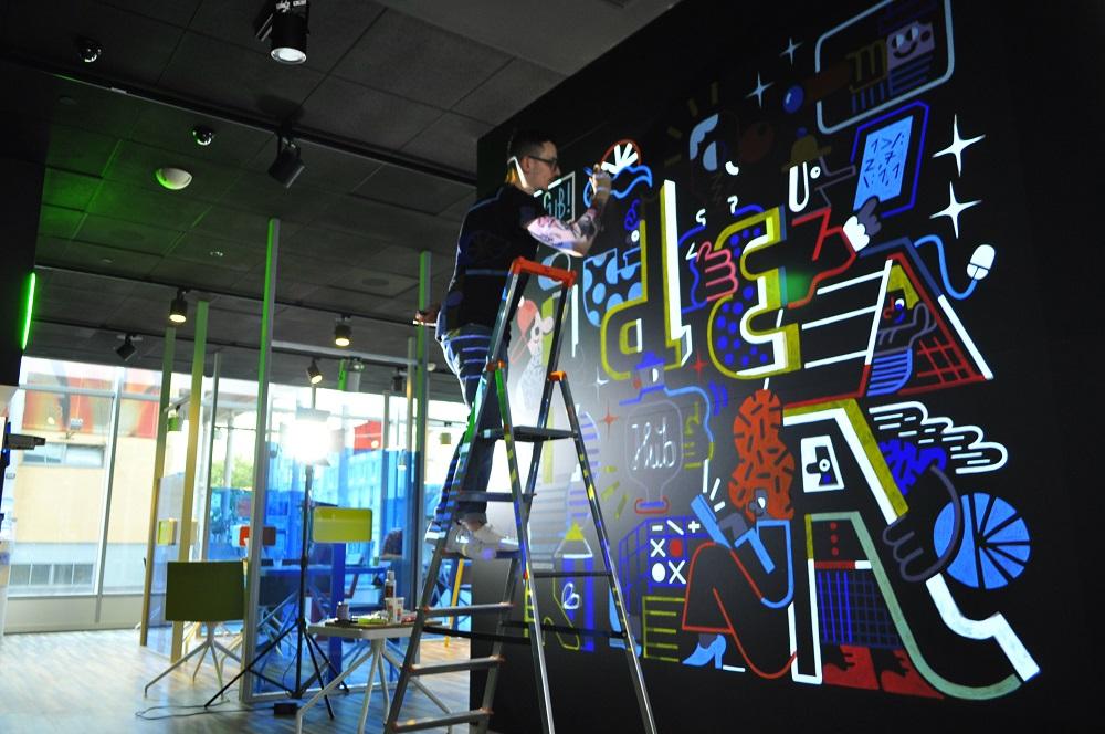 Artysta kończy swoje dzieło stojąc na drabinie i malując mural