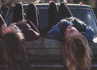 Dwie dziewczyny z długimi włosami leżą na masce samochodu