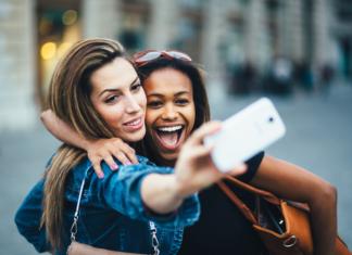 Dwie dziewczyny robią wspólne selfie białym smartfonem