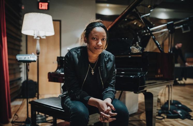 Dziewczyna w skórzanej kurtce siedzi obok fortepianu