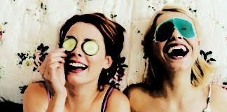 Dwie dziewczyny leżą na łóżku z maseczkami z ogórka