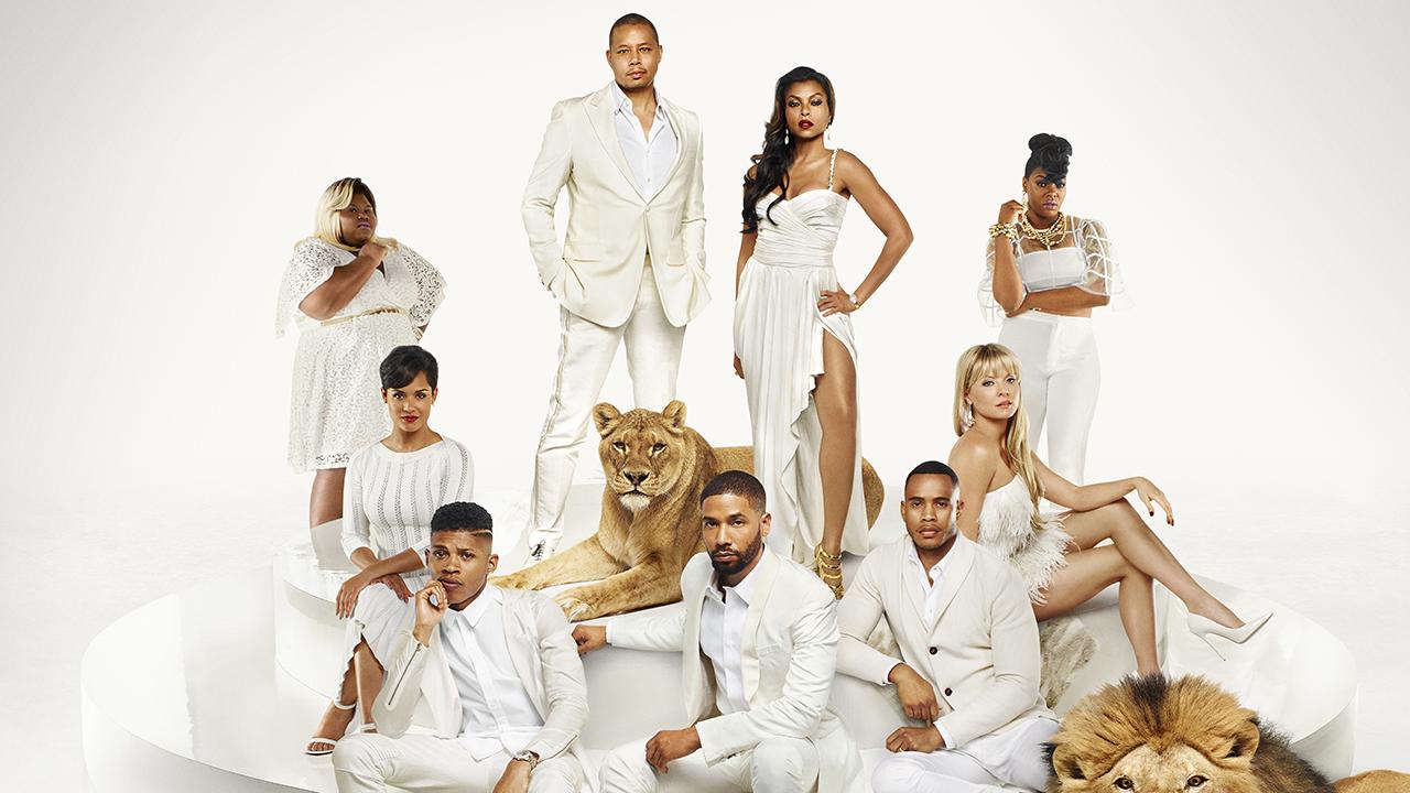 Grupa ubranych na biało pozuje do zdjęcia, obok dwa lwy