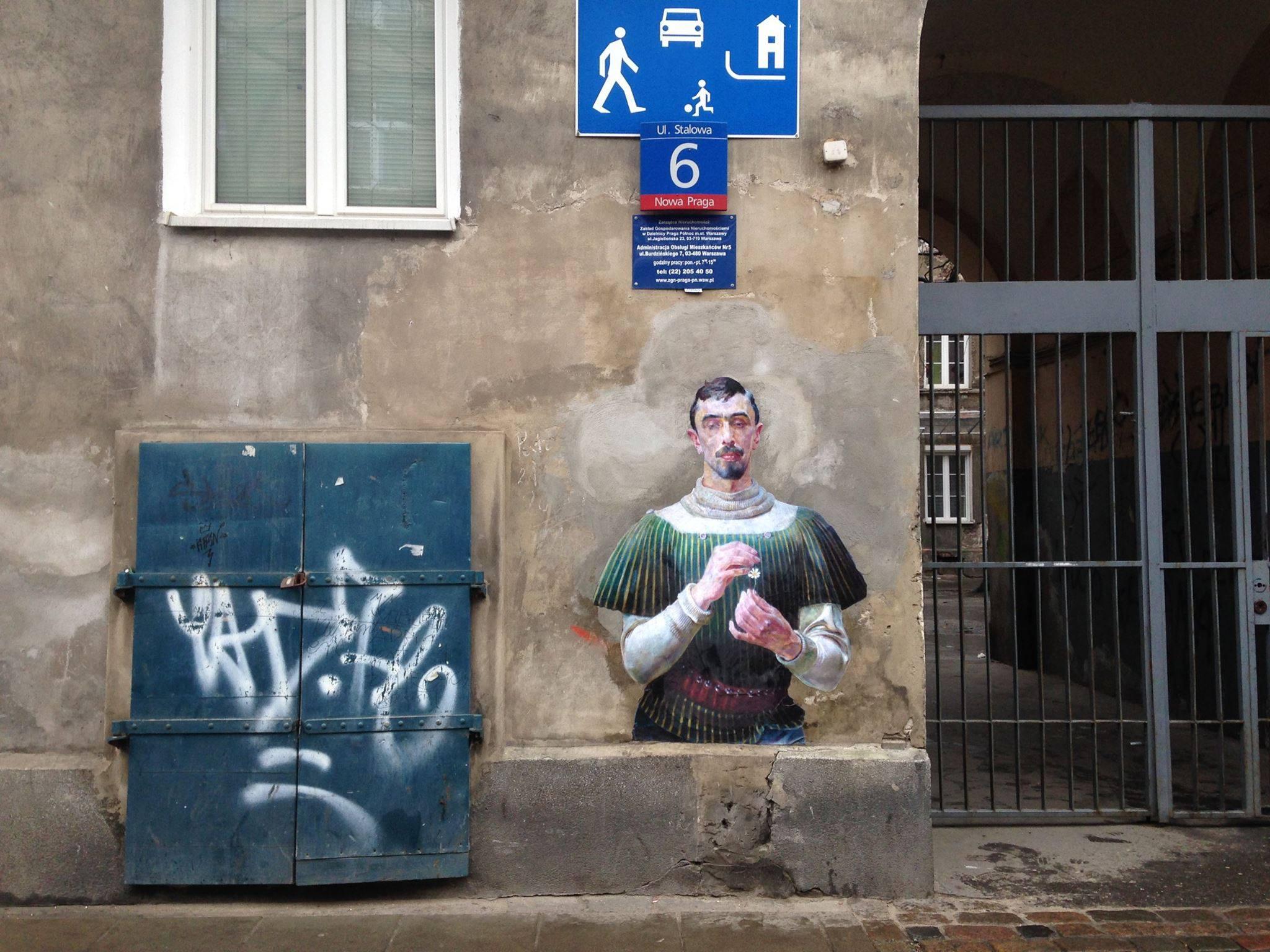 Fragment obrazu przyklejony na ścianę kamienicy