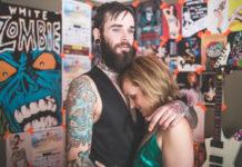 Chłopak w tatuażach przytula dziewczynę w zielonej sukience na tle ścian z graffiti