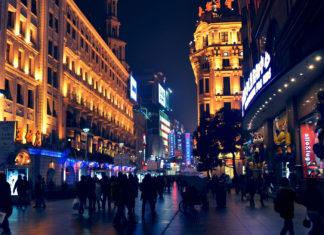 Oświetlone budynki i ulica pełna przechodniów nocą