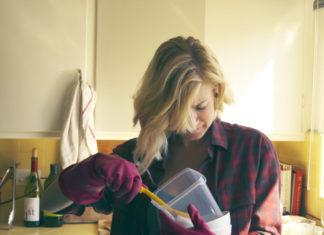 Blondynka w koszuli w kratkę myje naczynia