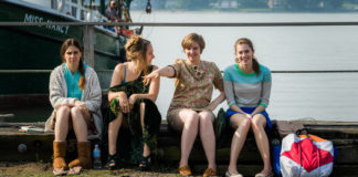 Cztery dziewczyny siedzą na molo