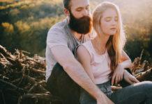 Mężczyzna brodą i blondynka siedzą na pniu