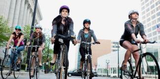 Pięciu rowerzystów w kaskach jedzie po ulicy