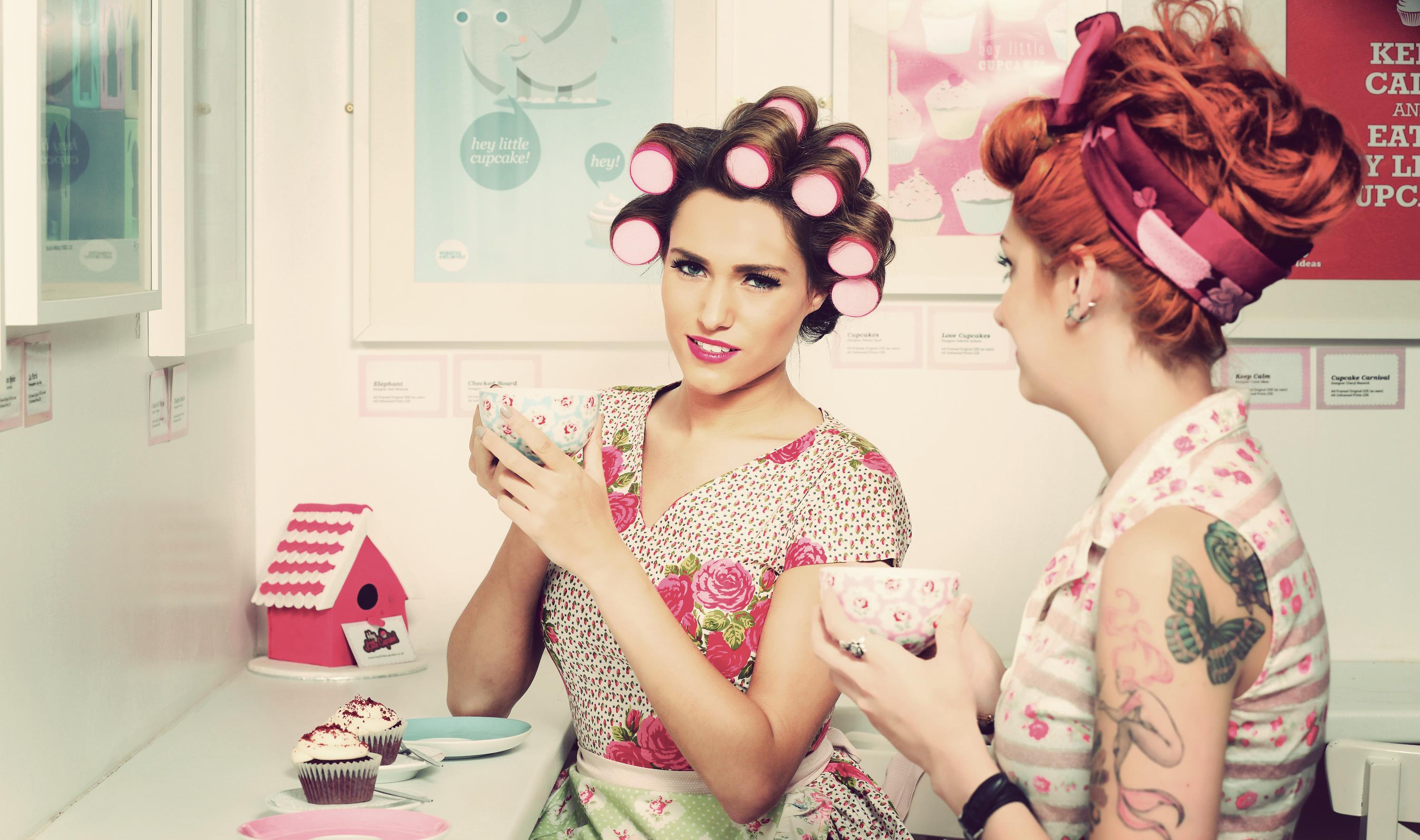 Dwie kobiety z wałkami na głowie w vintage ubaniach piją kawę