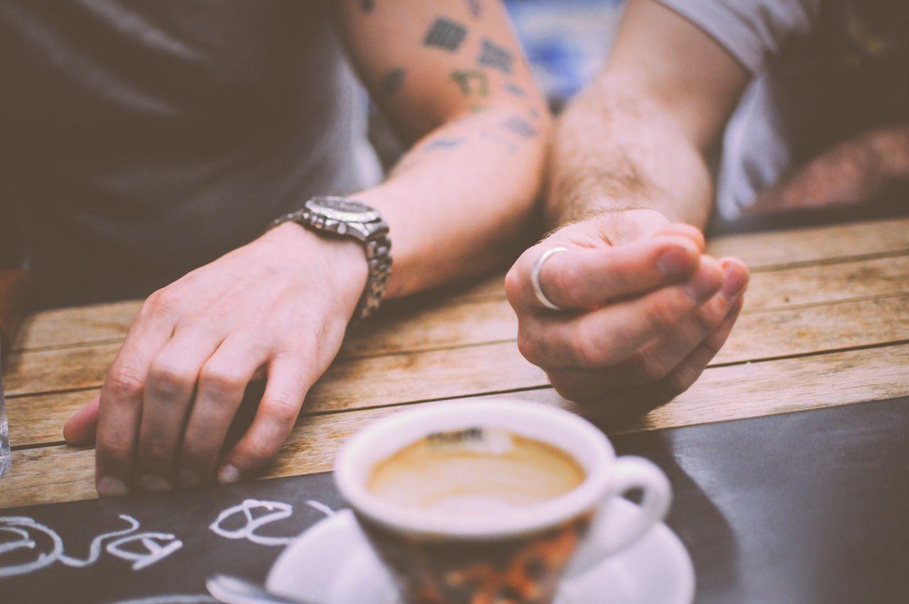 Męskie dłonie na blacie, obok filiżanka kawy