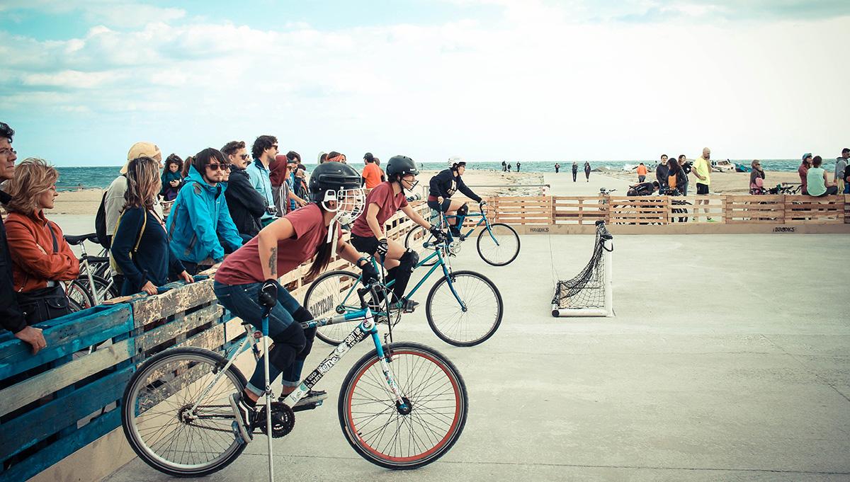 Grupa rowerzystów ściga się na zawodach, za nimi publiczność