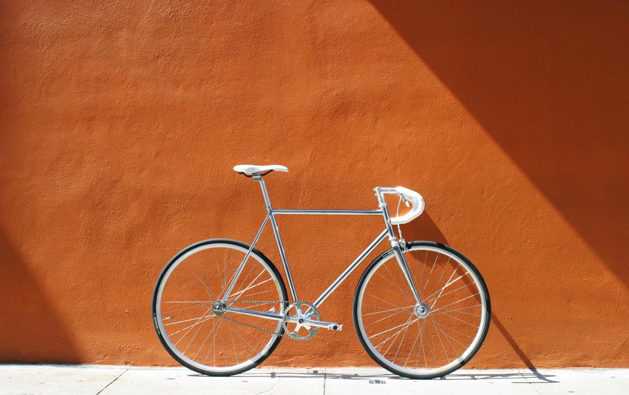 Srebrny rower na tle ceglanej ściany