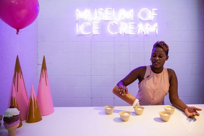 Ciemnoskóra kobieta w jasnej sukience robi lody, za nią napis