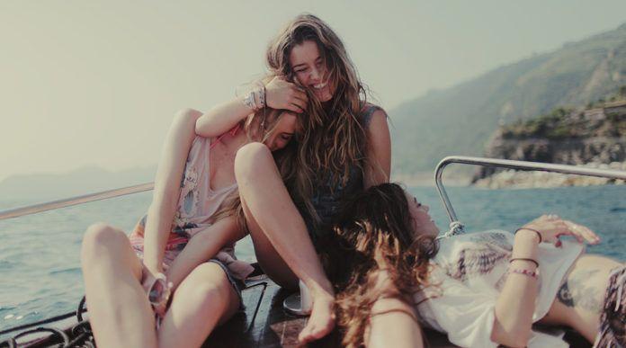 Grupa przyjaciółek siedzi na jachcie, przytula się, śmieje