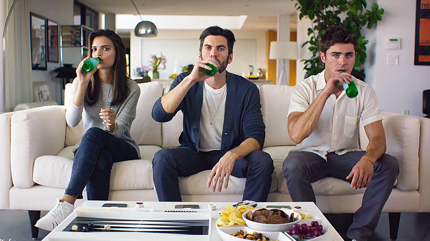 Brunetka pije piwo na kanapie w towarzystwie dwóch brunetów
