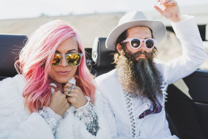 Kobieta z różowymi włosami i mężczyzna z długą czarną brodą ubrani na biało
