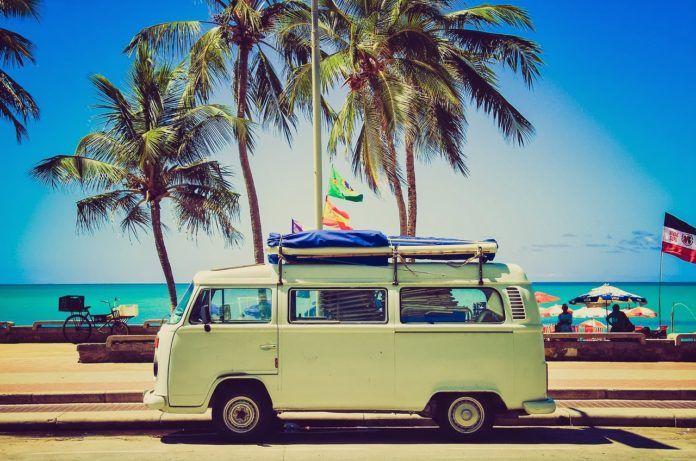 Seledynowa furgonetka na tle palm i oceanu