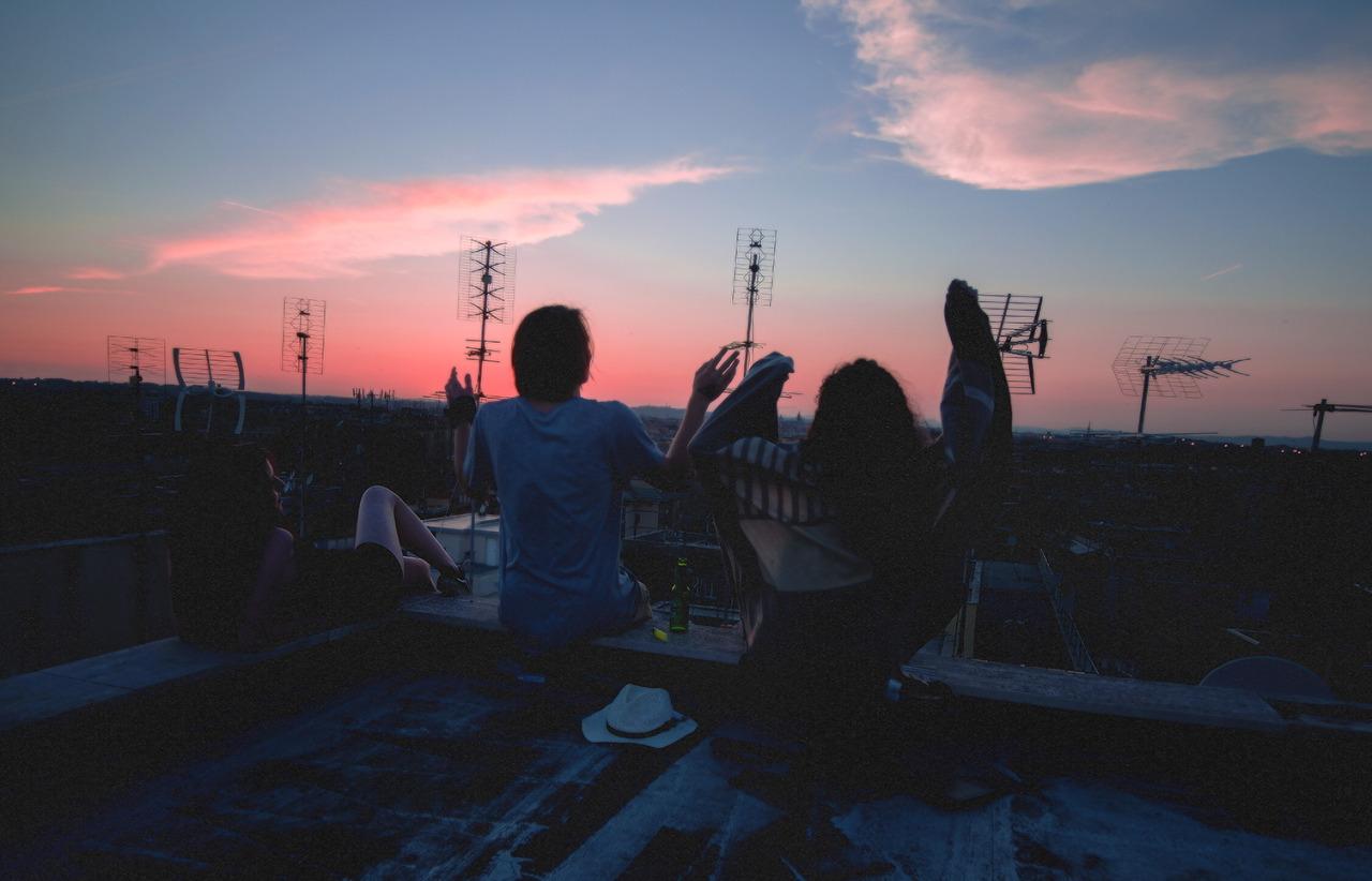 Chłopak i dziewczyna siedzą na dachu i podczas zachodu słońca