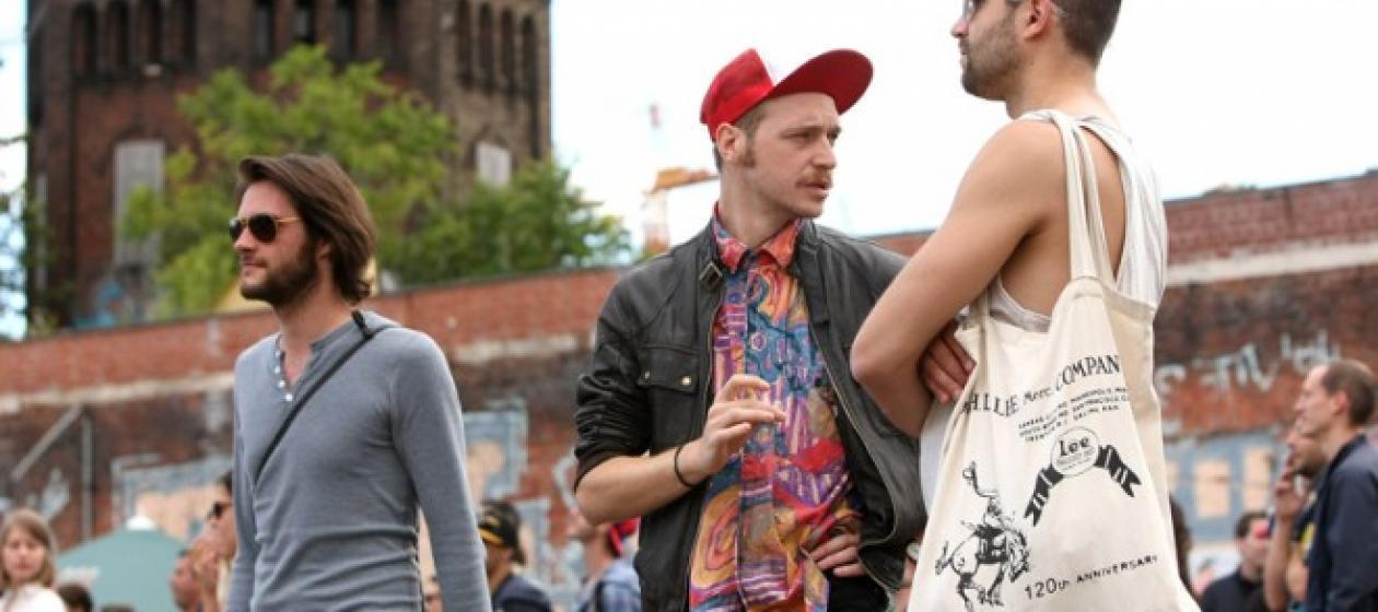 Trzech mężczyzn w letnich ubraniach w plenerze