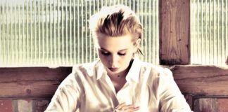 Blondynka w białej koszuli siedzi przy stole