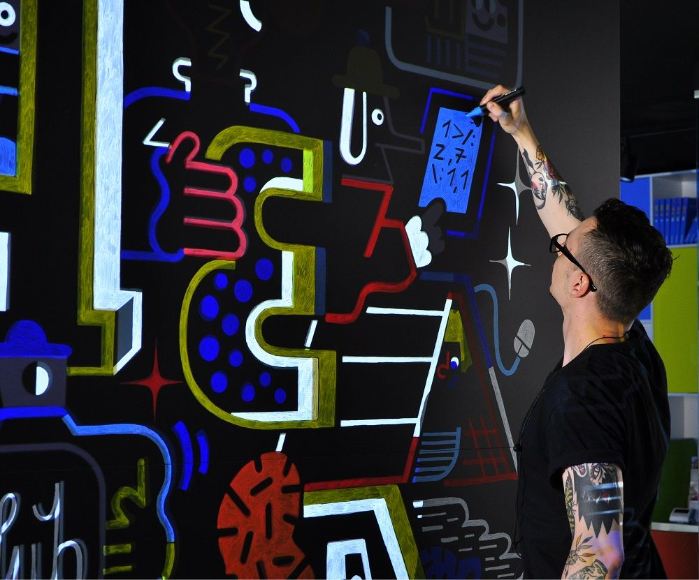 Artysta maluje mural stojąc