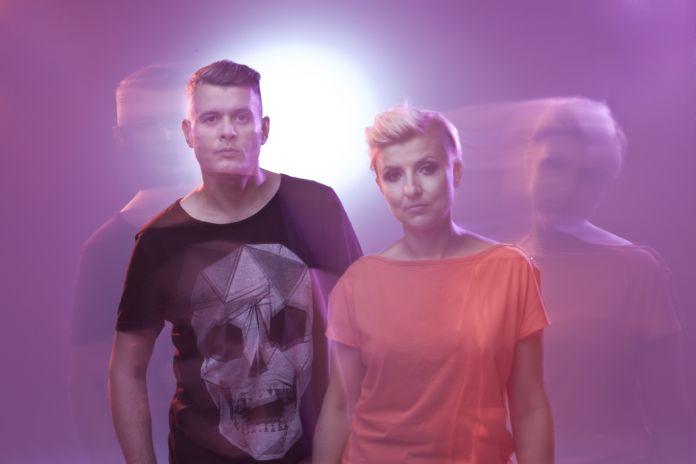 Blondynka i brunet stoją na różowym tle