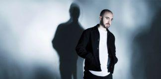 Mężczyzna w białej bluzce i czarnej kurtce na tle niebieskiej ściany