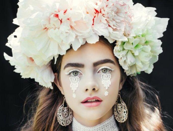 Dziewczyna w białym makijażu z wieńcem z kwiatów
