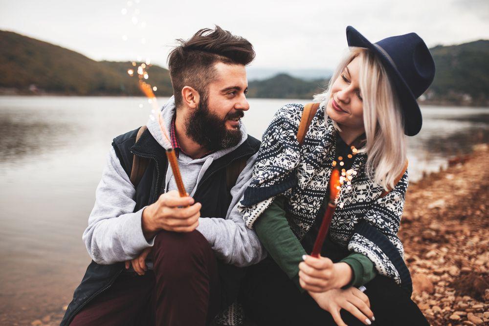 Blondynka i brunet patrzą na siebie, mają zimne ognie