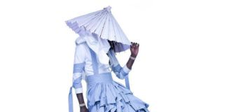 Postać w niebieskiej falbaniastej sukieknce i kapeluszu