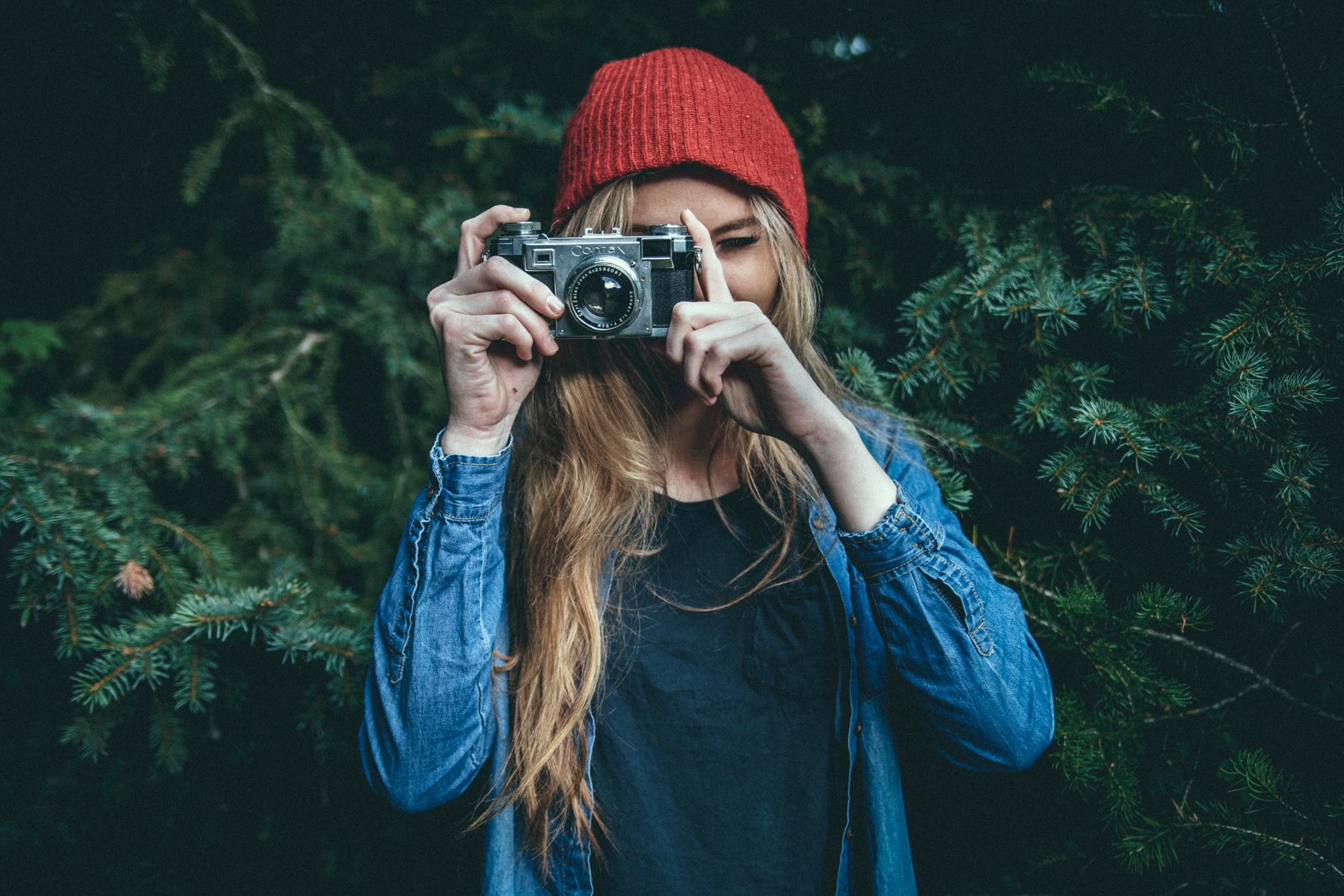 Dziewczyna ubrana na niebiesko w czerwonej czapce robi zdjęcie aparatem