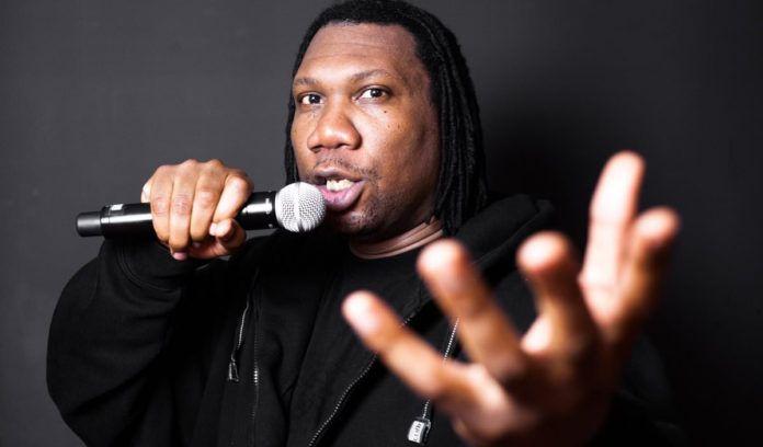 Ciemnoskóry mężczyzna ubrany na czarno z mikrofonem