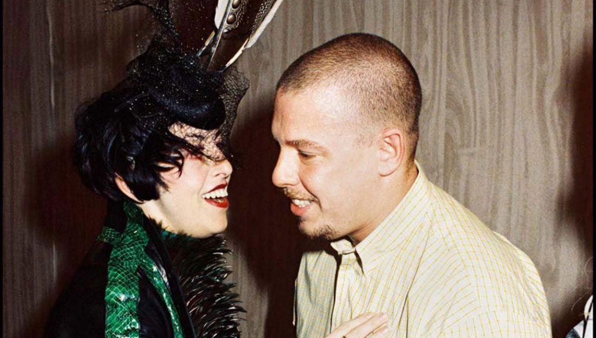 Kobieta w zielonej sukience i czarnym nakryciu głowy i mężczyzna w jasnym garniturze